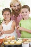 Mujer con dos niños que adornan las galletas Imagen de archivo