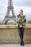 Mujer con el árbol de navidad delante de la torre Eiffel que mira a un lado Imagen de archivo