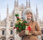 Mujer con el árbol de navidad y el regalo que miran en distancia, Milán Imágenes de archivo libres de regalías