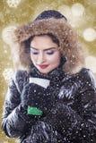 Mujer con el abrigo de invierno y el café caliente de los controles Foto de archivo libre de regalías