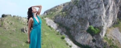 Mujer con el acantilado de la montaña rocosa en fondo Imagen de archivo libre de regalías