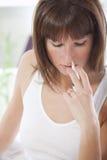 Mujer con el aerosol de nariz Imagen de archivo