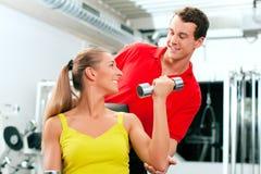Mujer con el amaestrador y pesas de gimnasia en gimnasia Fotos de archivo libres de regalías