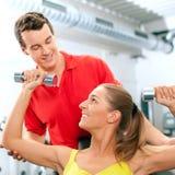Mujer con el amaestrador y pesas de gimnasia en gimnasia Foto de archivo