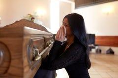 Mujer con el ataúd que llora en el entierro en iglesia fotografía de archivo