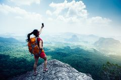 Mujer con el backpacker que camina en el borde del acantilado de la montaña de la playa Imagen de archivo libre de regalías