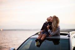 Mujer con el bebé en el tejado del coche Fotografía de archivo