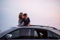 Mujer con el bebé en el tejado del coche Imagen de archivo libre de regalías