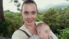Mujer con el bebé en la naturaleza tropical verde almacen de metraje de vídeo