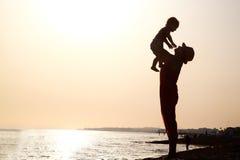 Mujer con el bebé en la puesta del sol imagen de archivo