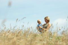 Mujer con el bebé en sus hombros en un país fotografía de archivo libre de regalías