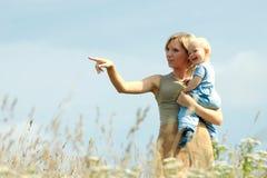 Mujer con el bebé en sus hombros en un país Imagen de archivo