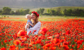 Mujer con el bebé en un campo de amapolas rojas Fotos de archivo