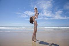 Mujer con el bebé para arriba en sus brazos Fotos de archivo