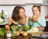 Mujer con el bebé que cocina en la cocina fotografía de archivo