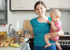 Mujer con el bebé que cocina los purés de patata Foto de archivo libre de regalías