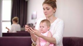 Mujer con el bebé que sostiene el teléfono en casa Madre de funcionamiento Vida cotidiana femenina almacen de metraje de vídeo