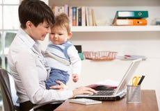 Mujer con el bebé que trabaja de hogar usando la computadora portátil Fotografía de archivo
