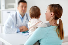 Mujer con el bebé y el doctor en la clínica Fotos de archivo