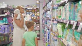 Mujer con el bebé y el hijo de la anciano que eligen los pañales en supermercado almacen de metraje de vídeo