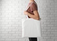 Mujer con el bolso del algodón cerca de la pared de ladrillo blanca foto de archivo
