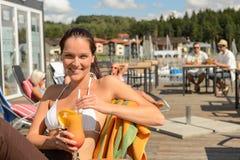 Cóctel de consumición de la mujer en la barra de la playa Foto de archivo libre de regalías