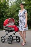 Mujer con el carro de bebé imagenes de archivo