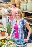 Mujer con el carro de compras en departamento del jardín Fotografía de archivo libre de regalías