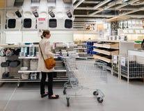 Mujer con el carro de la compra dentro de las decisiones de IKEA Fotografía de archivo