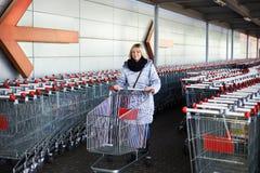 Mujer con el carro de la compra en el estacionamiento Imagenes de archivo