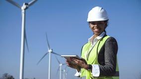 Mujer con el casco contra la turbina de viento Imágenes de archivo libres de regalías