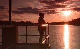 Mujer con el casco de la bicicleta por el lago en la puesta del sol Foto de archivo