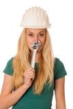 Mujer con el casco del constructor y herramientas que gesticulan la nariz sofocante Imagenes de archivo