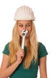 Mujer con el casco del constructor y herramientas que gesticulan la nariz sofocante Imagen de archivo libre de regalías