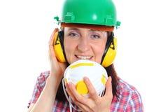 Mujer con el casco que lleva y los auriculares de la máscara protectora Fotografía de archivo
