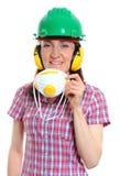 Mujer con el casco que lleva y los auriculares de la máscara protectora Fotografía de archivo libre de regalías