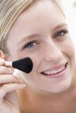 Mujer con el cepillo del maquillaje Imagenes de archivo