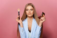 Mujer con el cepillo y el espejo del maquillaje fotos de archivo