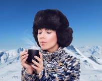 Mujer con el chocolate caliente en las montañas nevosas, estación del invierno Foto de archivo