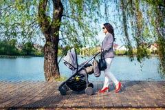 Mujer con el cochecito en cubierta del lago en parque de la ciudad Niño que camina de la madre feliz con el cochecito de niño Fotografía de archivo