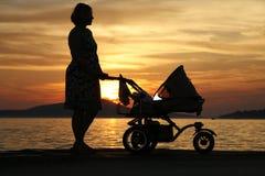 Mujer con el cochecito en la puesta del sol imagen de archivo libre de regalías
