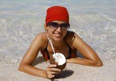Mujer con el coco en la playa foto de archivo