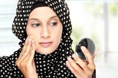Mujer con el cojín de algodón que aplica el polvo de cara Imágenes de archivo libres de regalías
