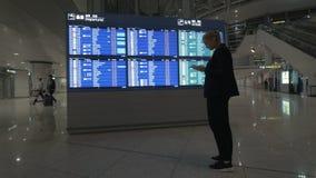 Mujer con el cojín que mira el calendario del vuelo metrajes