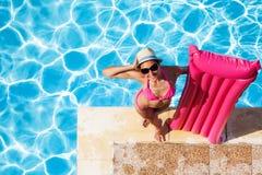 Mujer con el colchón inflable rosado en el poolside foto de archivo