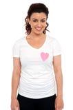 Mujer con el corazón de papel rosado en su camiseta imagen de archivo