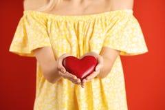 Mujer con el corazón decorativo en fondo del color foto de archivo
