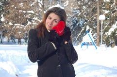 Mujer con el corazón del amor en nieve Fotografía de archivo