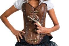 Mujer con el corsé de cuero que lleva del arma antiguo foto de archivo