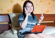 Mujer con el cuaderno, el teléfono y de la tarjeta de crédito Foto de archivo libre de regalías